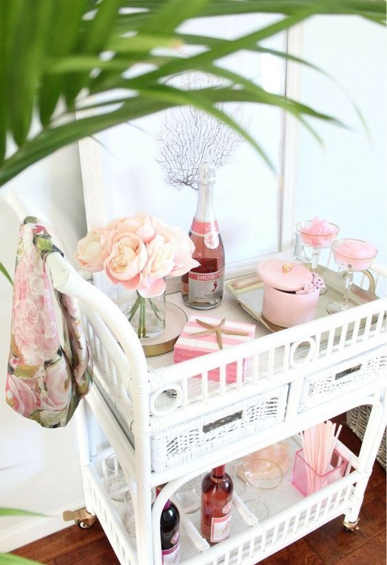 a blush pink bar cart with some blush blooms, boxes and straws is a cute idea