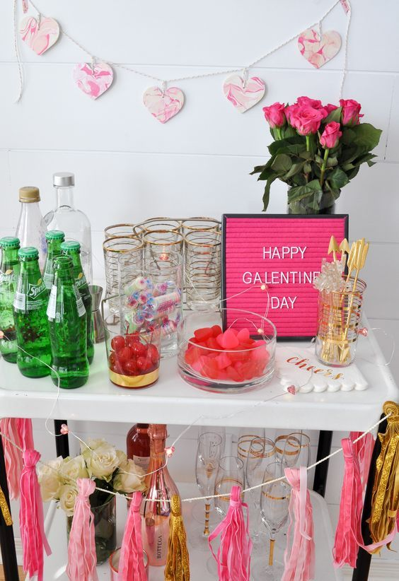 a bright Galentine party bar cart with a marble heart and tassel garland, with pink roses and a pink sign