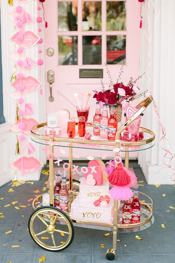 a colorful bar cart with burgundy and blush blooms, hot pink tassels and hearts all over