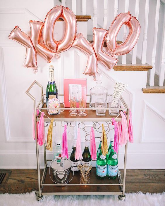 a cute Valentine bar cart styled with large XO letters and a neon tassel garland