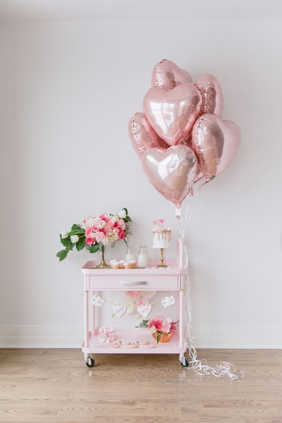 a cute blush bar cart with metallic pink heart balloons, a heart bunting and a floral centerpiece in pink and white
