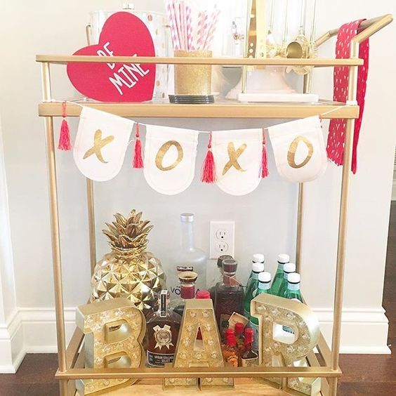 a glam Valentine bar cart with a XO bunting, a pink heart and a gold BAR marquee light
