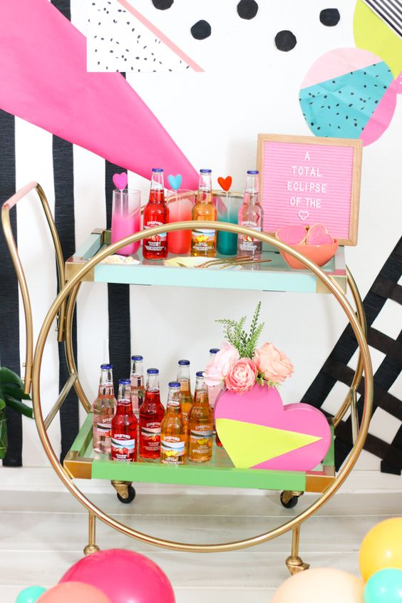 a modern glam bar cart with neon touches   pink, yellow and green, hearts and a pink sign