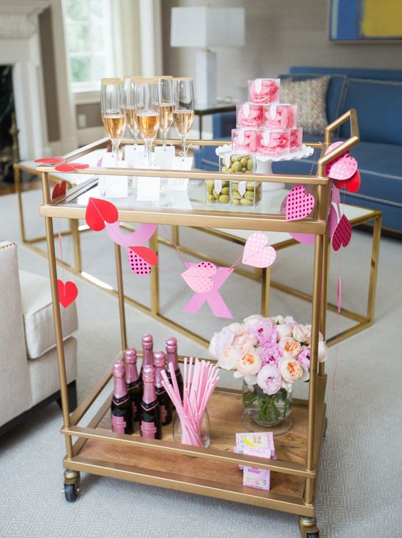 a romantic Valentine bar cart with a paper buntign in red and pink, with pastel blooms and everything pink