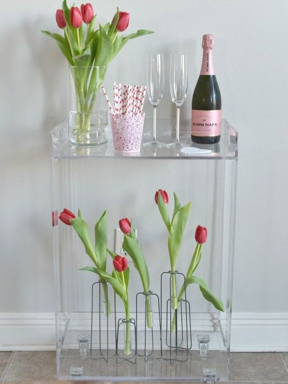 an ultra-modern acrylic bar cart styled with red tulips in sheer vases for Valentine's Day