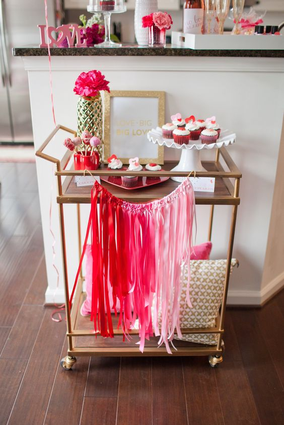 colorful Valentine bar cart styling with an ombre tassel bunting and hot pink blooms
