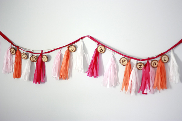 DIY burnt wood slices and colorful tassels banner (via amber-oliver.com)