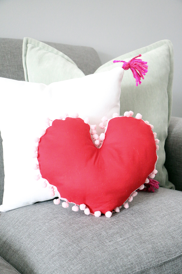 DIY red heart-shaped pillow with white pompoms (via happinessiscreating.com)