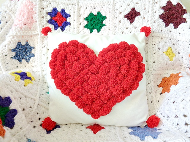 DIY white pillow with a red pompom heart (via www.seamsandscissors.com)