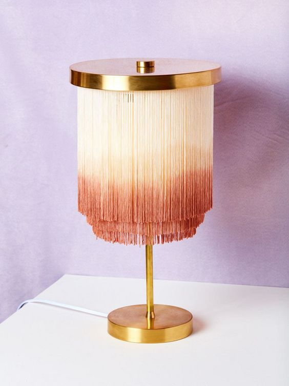a bold gold lamp with long ombre fringe from creamy to pink hanging down will make a statement
