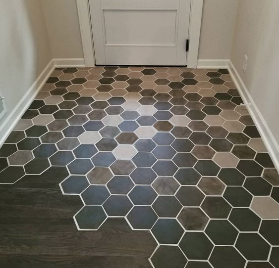 a chic seamless floor transition from colorful hex tiles into dark laminate is a gorgeous idea