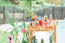 03 a bar cart with pineapples, lush blooms and some potted plants by its side
