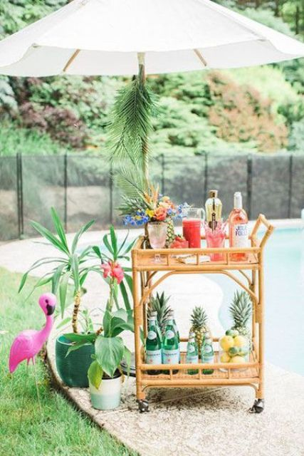 a bar cart with pineapples, lush blooms and some potted plants by its side