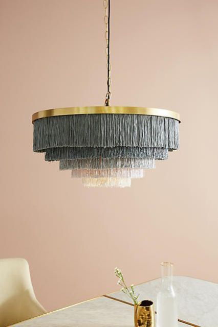 a brass lamp with long grey fringe and an ombre effect in layers to accent a space