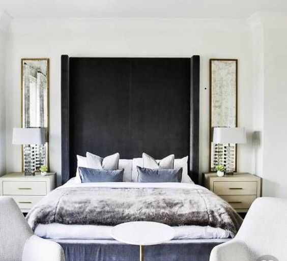 an extra tall upholstered wingback headboard in a dark shade contrasts the whole neutral space