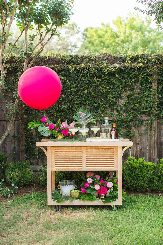 a bold tropical bar cart with pink  blooms, balloons and monstera leaves for decor
