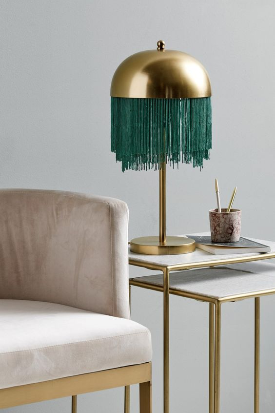 a brass lamp with a rounded lampshade and long emerald fringe hanging down for a catchy look