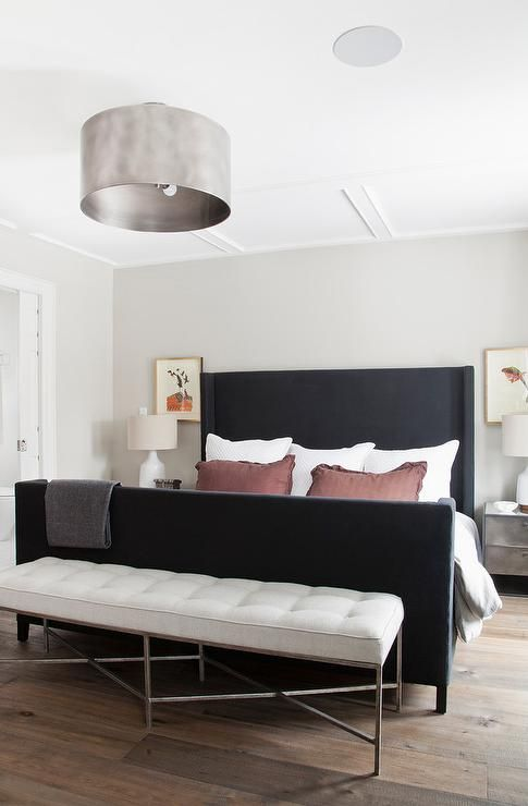 a black wingback bed with a bench in cream is a bold combo for a monochromatic space