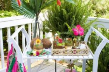 05 a colorful tropical bar cart with coconuts, a colorful tassel garland and bright tropical blooms