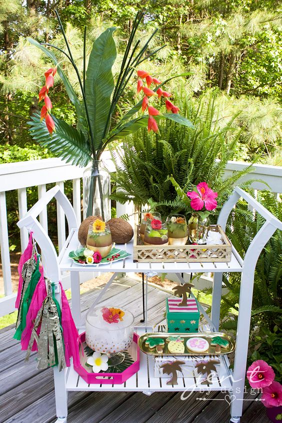 a colorful tropical bar cart with coconuts, a colorful tassel garland and bright tropical blooms