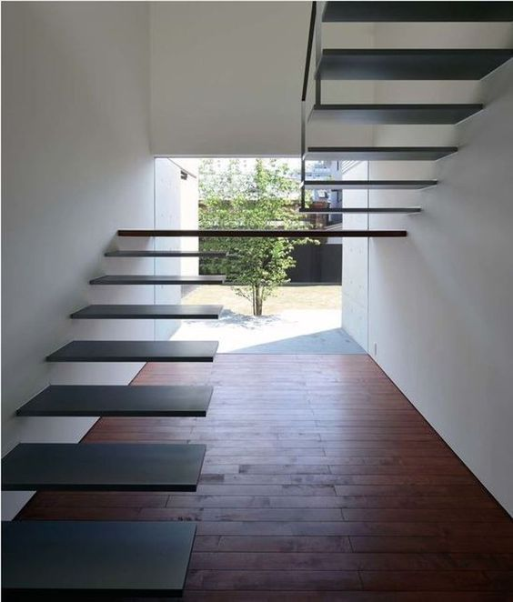 a fully floating metal staircase attached to the wall with a large platform floating