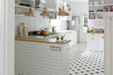 05 black and white mosaic tiles in the kitchen, whitewashed laminate in the rest of the space