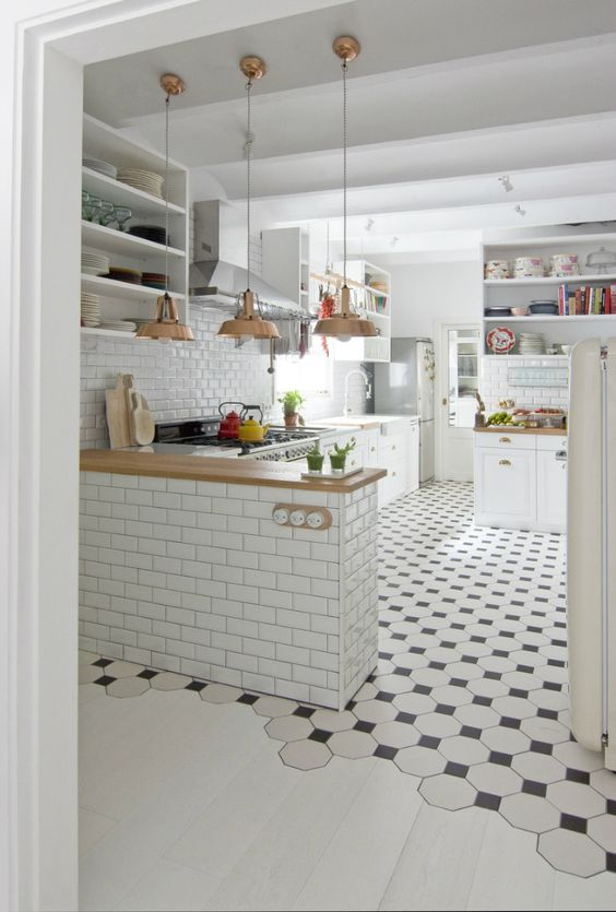 black and white mosaic tiles in the kitchen, whitewashed laminate in the rest of the space
