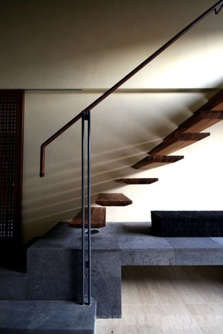 a chic floating staircase attached to the wall and metal railing for a bold look