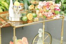 06 a luxurious tropical bar cart with citrus, lush blooms, greenery and a fruit stand