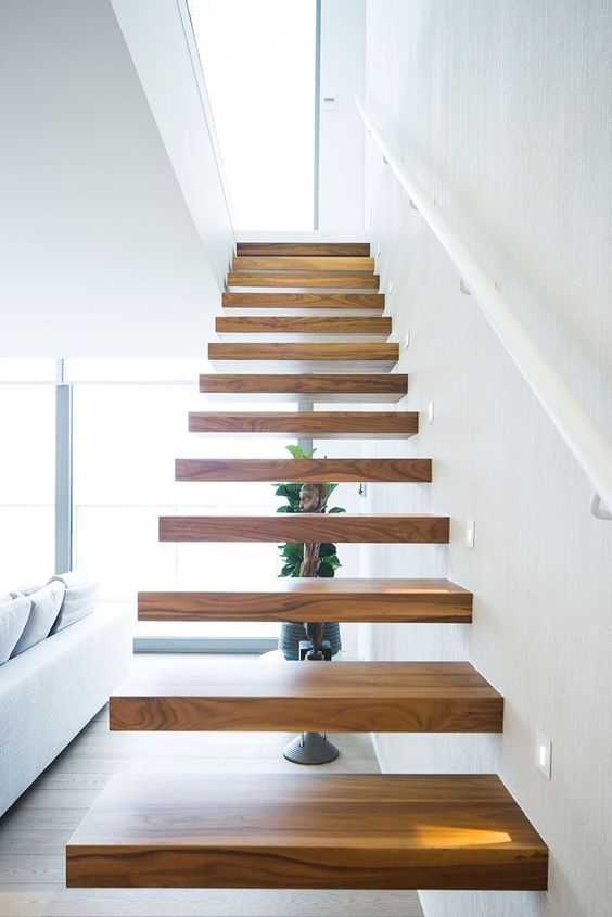 a floating staircase with no railing and banister creates a modern floating look than with them