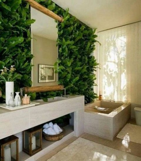 a super lush greenery wall with tropical leaves makes the minimalist bathroom vibrant and fresh