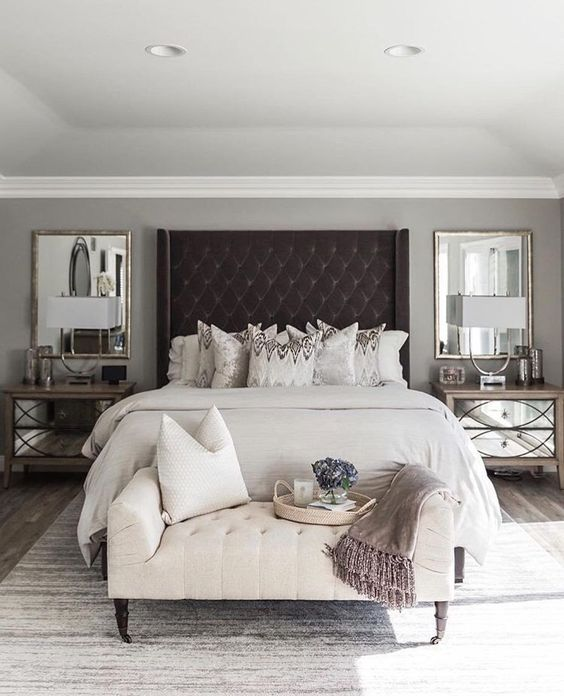 an oversized black upholstered wingback headboard takes over the whole neutral bedroom