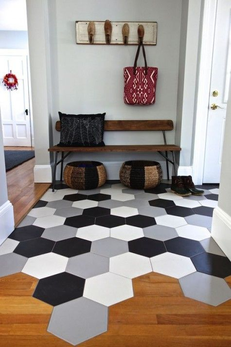 large scale hexagon tiles in different colors in the entryway flow into wamr-colored laminate in the rest of the space
