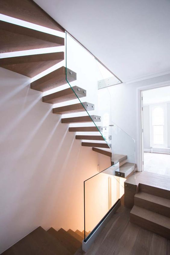 a floating staircase with steps attached to a glass banister looks very edgy and fresh