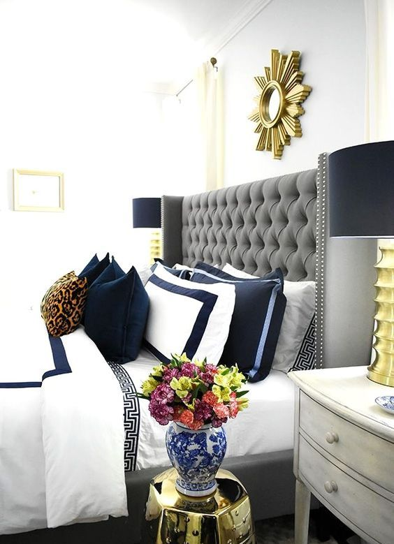 a grey tufted wingback headboard decorated with a nail trim is a chic and timeless idea