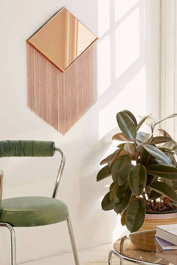 a geometric copper mirror with long copper fringe is a nod to boho chic and mid-century modern spaces
