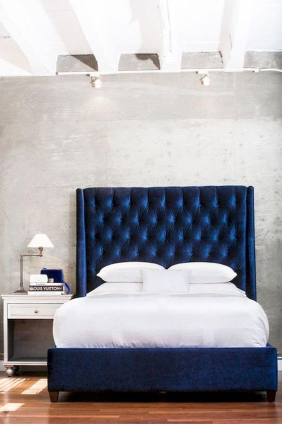 a navy upholstered bed with an oversized wingback headboard is a bold centerpiece for a bedroom