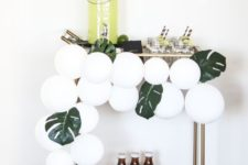 10 simple styling with white balloons and monstera leaves will be enough for a modern tropical party