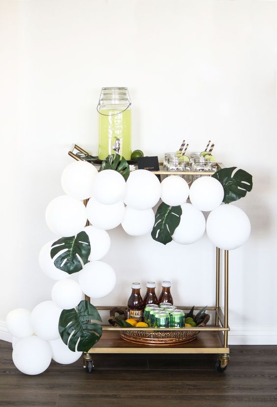 simple styling with white balloons and monstera leaves will be enough for a modern tropical party