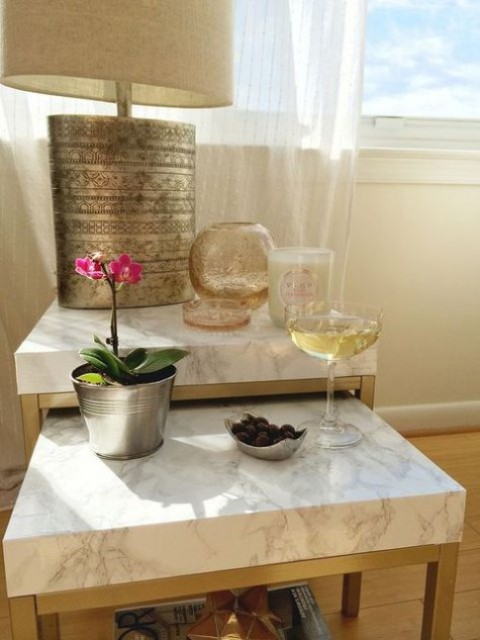 a duo of IKEA Lack tables renovated with marble contact paper and gold spray paint