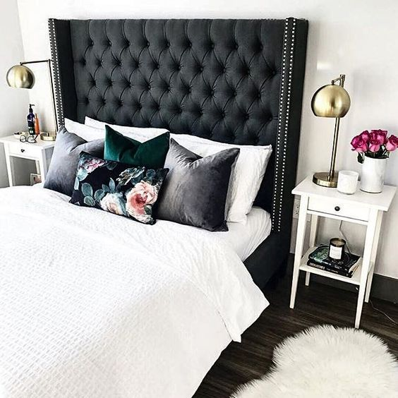 an oversized black tufted wingback headboard with a nail trim takes over the whole neutral space