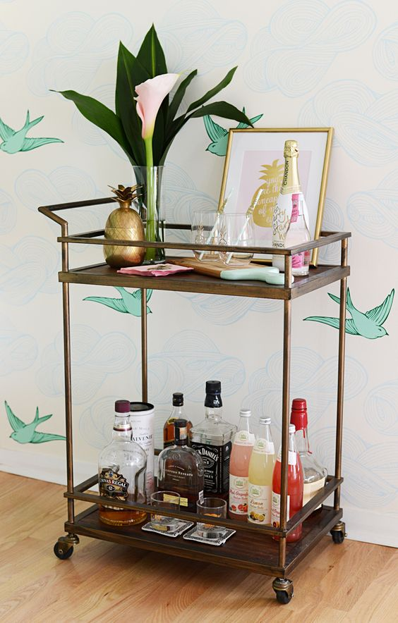 a styling idea of a bar cart with tropical leaves