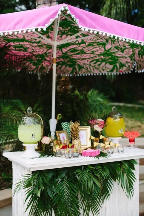 a bar decorated with lush tropical greenery and a pink umbrella on top is a simple and modern idea