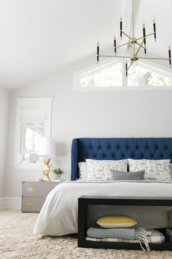 a bright blue bed with a tufted wingback headboard plus gold touches create an elegant space