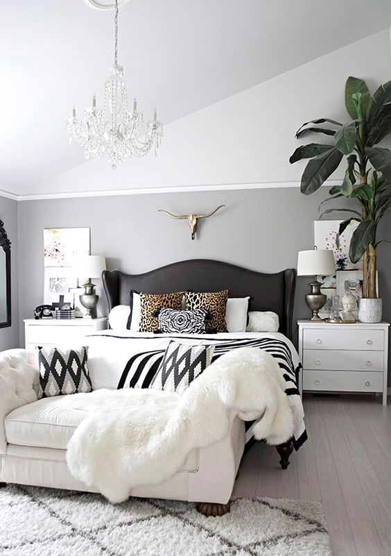a black vintage bed with a wingback leather headboard and an arrangement of printed pillows