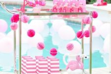 13 a hot pink flamingo bar cart with a pink garland, striped favor bags and pink bottles