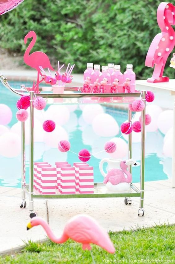a hot pink flamingo bar cart with a pink garland, striped favor bags and pink bottles