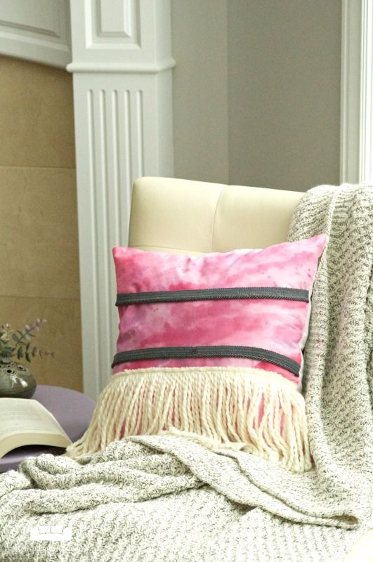 a pink boho chic pillow with long neutral fringe is a cool idea to accessorize your space