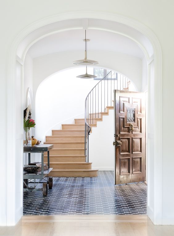 navy and white mosaic tiles in the entryway and a sharp transition to neutral laminate in the rest of the space