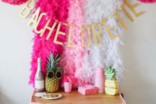 14 a tropical bachelorette bar cart styled with natural and fake pineapples and lush pink garlands over it
